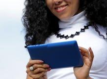 Jovem mulher que usa uma tabuleta no fundo do céu Fotos de Stock
