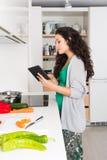 Jovem mulher que usa uma tabuleta para cozinhar Imagens de Stock Royalty Free