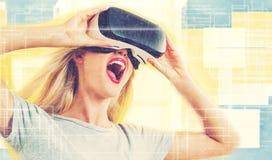 Jovem mulher que usa uns auriculares da realidade virtual Imagens de Stock