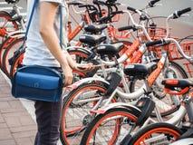 Jovem mulher que utiliza a bicicleta de Mobike que compartilha do sistema fotos de stock