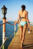 Jovem mulher que vai em uma ponte no mar, vista traseira imagens de stock royalty free