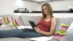 Jovem mulher que verifica as finanças em casa que usam a tabuleta de Digitas filme