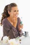 Jovem mulher que verifica os dentes após a escovadela foto de stock royalty free