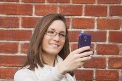 Jovem mulher que verifica a rua do telefone celular Fotos de Stock Royalty Free