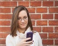 Jovem mulher que verifica a rua do telefone celular Fotografia de Stock Royalty Free
