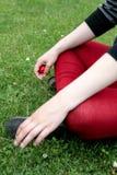 Jovem mulher que veste as caneleiras vermelhas sentadas na grama imagens de stock royalty free