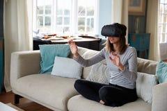 Jovem mulher que veste auriculares da realidade virtual no estúdio Imagens de Stock