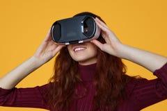 Jovem mulher que veste auriculares de VR Foto de Stock