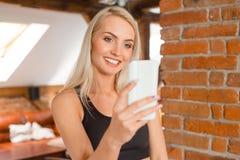 A jovem mulher que veste esportes veste a tomada do selfie usando o telefone foto de stock royalty free