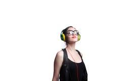 Jovem mulher que veste grandes vidros quadro pretos e que escuta Imagem de Stock Royalty Free