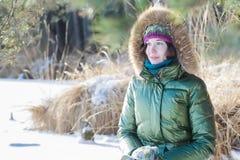 A jovem mulher que veste a guarnição real encapuçado verde da pele reveste para baixo a apreciação da vista na floresta do invern Foto de Stock