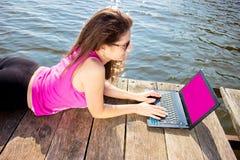 Jovem mulher que veste na camisa cor-de-rosa que senta-se na ponte do lago usando o laptop imagens de stock royalty free