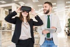 Jovem mulher que veste o capacete de VR imagem de stock