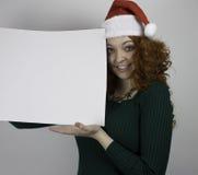 Jovem mulher que veste o chapéu de Santa que guarda o sinal vazio Fotografia de Stock Royalty Free