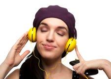 Jovem mulher que veste o vestido preto do às bolinhas e que escuta Headp Foto de Stock Royalty Free