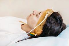 A jovem mulher que veste os auriculares da exploração do brainwave senta-se em uma cadeira no centro de Brain Study Laboratory Ne fotos de stock royalty free