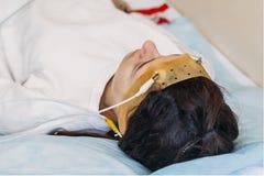 A jovem mulher que veste os auriculares da exploração do brainwave senta-se em uma cadeira no centro de Brain Study Laboratory Ne imagens de stock
