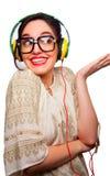 Jovem mulher que veste os grandes vidros quadro pretos que escutam a cabeça Fotografia de Stock Royalty Free