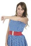 Jovem mulher que veste a polca azul Dot Dress Thumbs para baixo Imagens de Stock