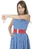 Jovem mulher que veste a polca azul Dot Dress Thumbs para baixo Imagem de Stock Royalty Free