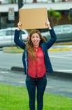 Jovem mulher que veste a roupa ocasional que está fora de sustentação o cartaz do cartão, protestando o conceito fotos de stock