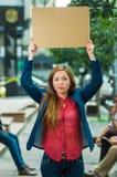 Jovem mulher que veste a roupa ocasional que está fora de sustentação o cartaz do cartão, protestando o conceito imagens de stock