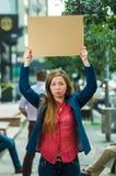 Jovem mulher que veste a roupa ocasional que está fora de sustentação o cartaz do cartão, protestando o conceito imagem de stock