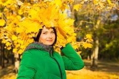 Jovem mulher que veste um chapéu das folhas de outono amarelas Imagens de Stock