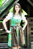 Jovem mulher que veste um dirndl que está no alojamento de madeira imagens de stock royalty free