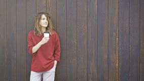 A jovem mulher que veste uma camiseta vermelha está bebendo o café para ir ao estar perto de uma parede de madeira Tiro médio Fotos de Stock Royalty Free