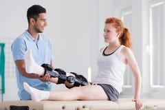 Jovem mulher que veste uma cinta durante a reabilitação com seu fisioterapeuta foto de stock