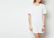Jovem mulher que veste a veste longa vazia e o relógio digital Fundo branco fotos de stock royalty free