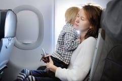 Jovem mulher que viaja com sua criança pequena por um avião Fotografia de Stock