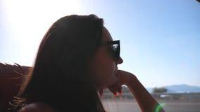 Jovem mulher que viaja pelo ônibus no verão e que olha à janela Menina nos óculos de sol que olha para fora a janela durante a vi vídeos de arquivo