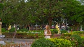 Jovem mulher que visita um templo de Wat Chalong na ilha de Phuket, Tailândia video estoque