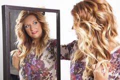 Jovem mulher real que olha em um espelho Fotografia de Stock Royalty Free