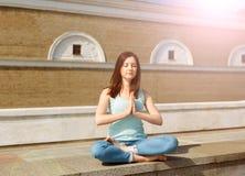 A jovem mulher relaxa dentro a pose na parte dianteira de uma parede de tijolo Imagem de Stock