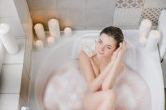 A jovem mulher relaxa em um banho quente completamente da espuma fotos de stock royalty free