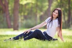 A jovem mulher relaxa no parque na grama verde Natureza da beleza imagens de stock royalty free