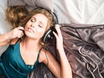 Jovem mulher relaxado ao escutar o jogador de música através dos fones de ouvido na cama confortável Imagem de Stock Royalty Free