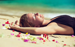 Jovem mulher relaxado que encontra-se na areia Foto de Stock
