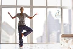 Jovem mulher relaxado que exercita em casa imagens de stock royalty free