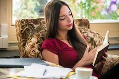 Jovem mulher relaxado que lê um livro dentro imagem de stock