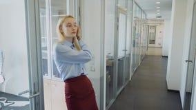 A jovem mulher retira o escritório e anda abaixo do corredor na empresa video estoque