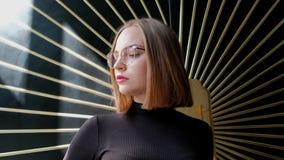 Jovem mulher ruivo atrativa com um corte de cabelo curto em um quadrado, em uns vidros vestindo e em uma gola alta marrom contra  vídeos de arquivo
