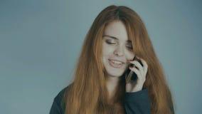 Jovem mulher ruivo que fala no telefone e que sorri no fundo do estúdio, emoções do conceito, uma comunicação, tecnologia filme