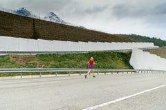 Jovem mulher running na estrada serpentina no pico nevado do fundo da montanha Imagens de Stock Royalty Free