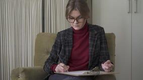 Jovem mulher séria nos vidros que escreve em uma prancheta filme