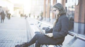 Jovem mulher séria nos vidros que olham seu portátil na rua Fotos de Stock Royalty Free