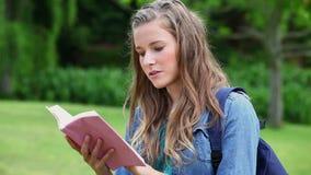 Jovem mulher séria que lê uma novela video estoque